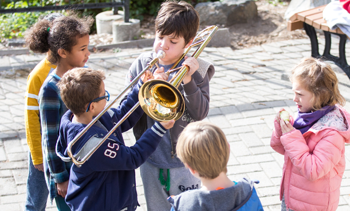 Young children in school yard gathered around boy playing trombone